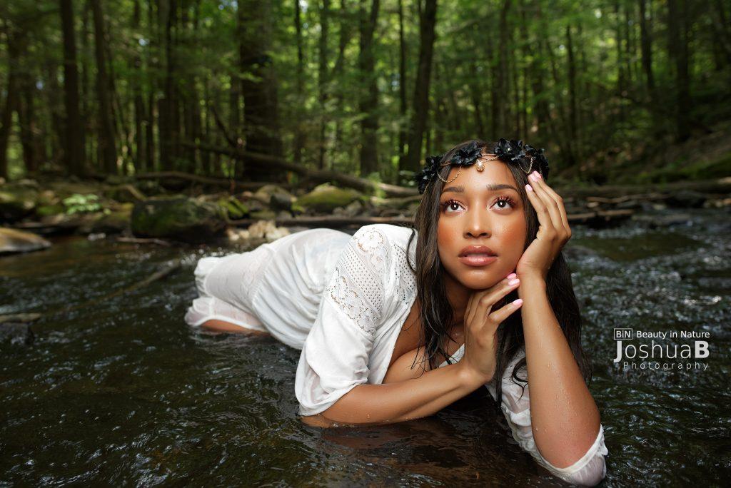 beautiful black woman, wet in white dress in river