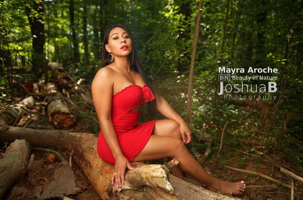 Beautiful Latina woman in woods wearing red dress