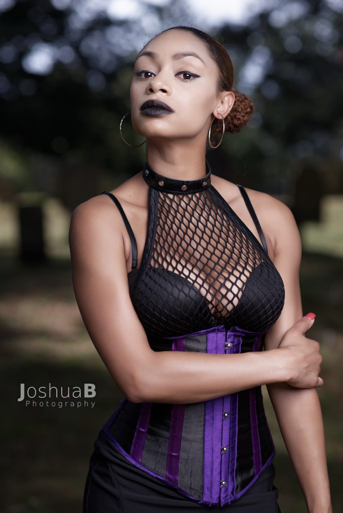 Beautiful Latina in sexy corset & fishnet top for Halloween holding arm