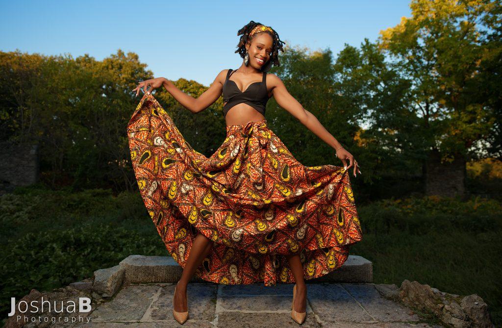 Beautiful black woman with dreadlocks modeling African print skirt in Boston