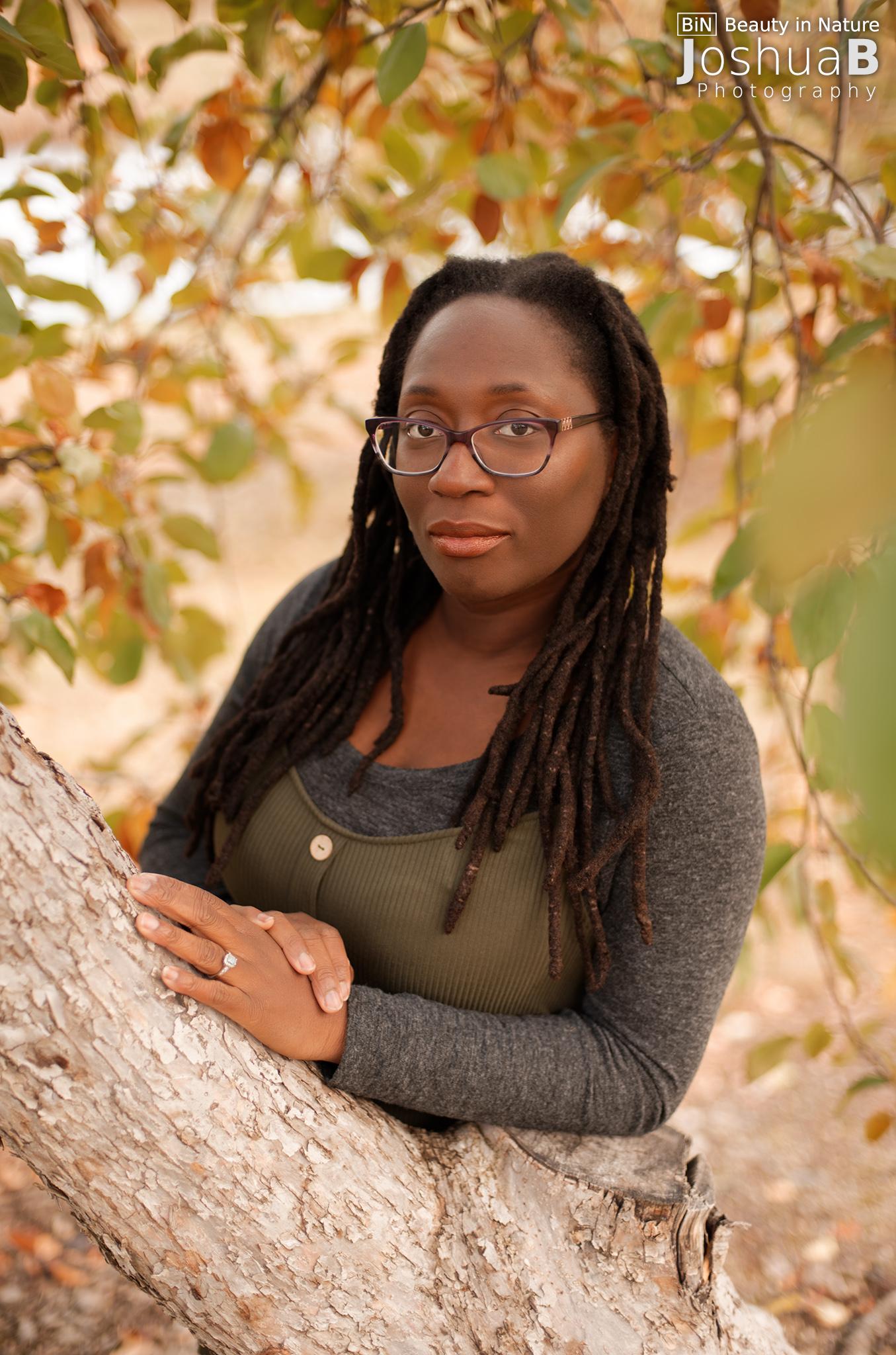Black woman with dreadlocks under apple tree
