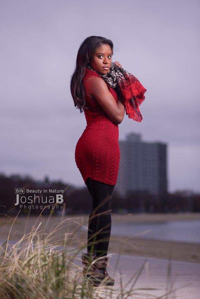 Beautiful black woman at beach modeling, looking back at camera