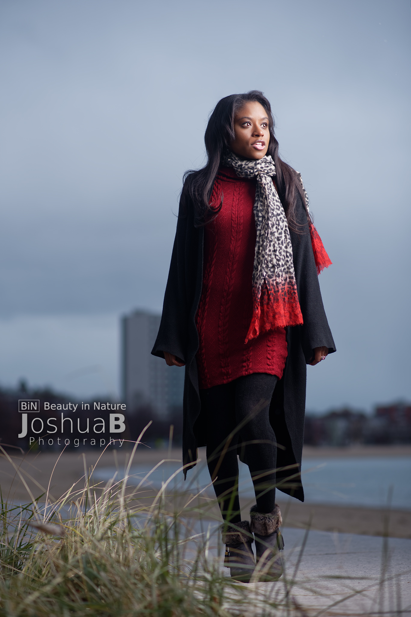 Beautiful young black woman modeling in sweater and scarf at Carson Beach