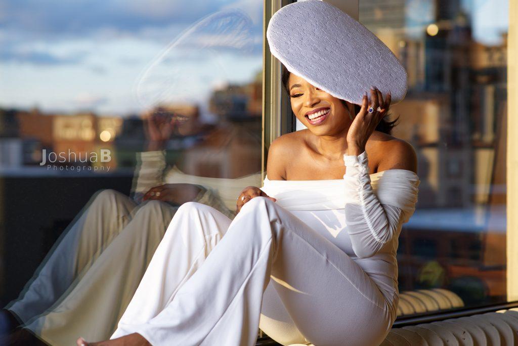 Abidemi Oke modeling in white suit hat at window