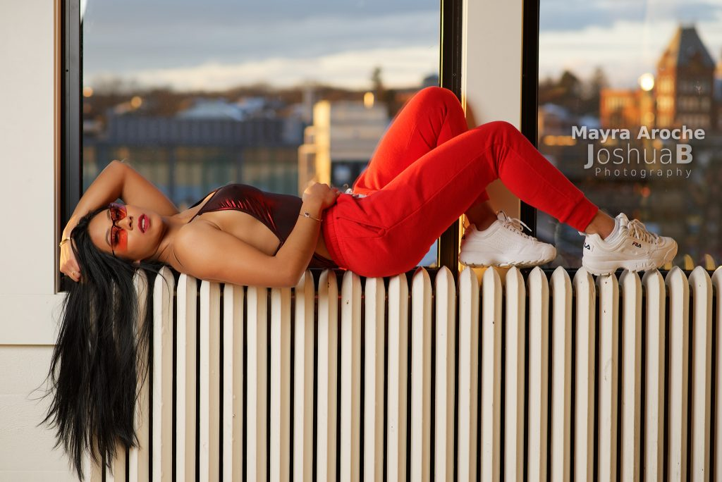 Mayra Aroche lying on back at window modeling in red bodysuit sweat pants unglasses