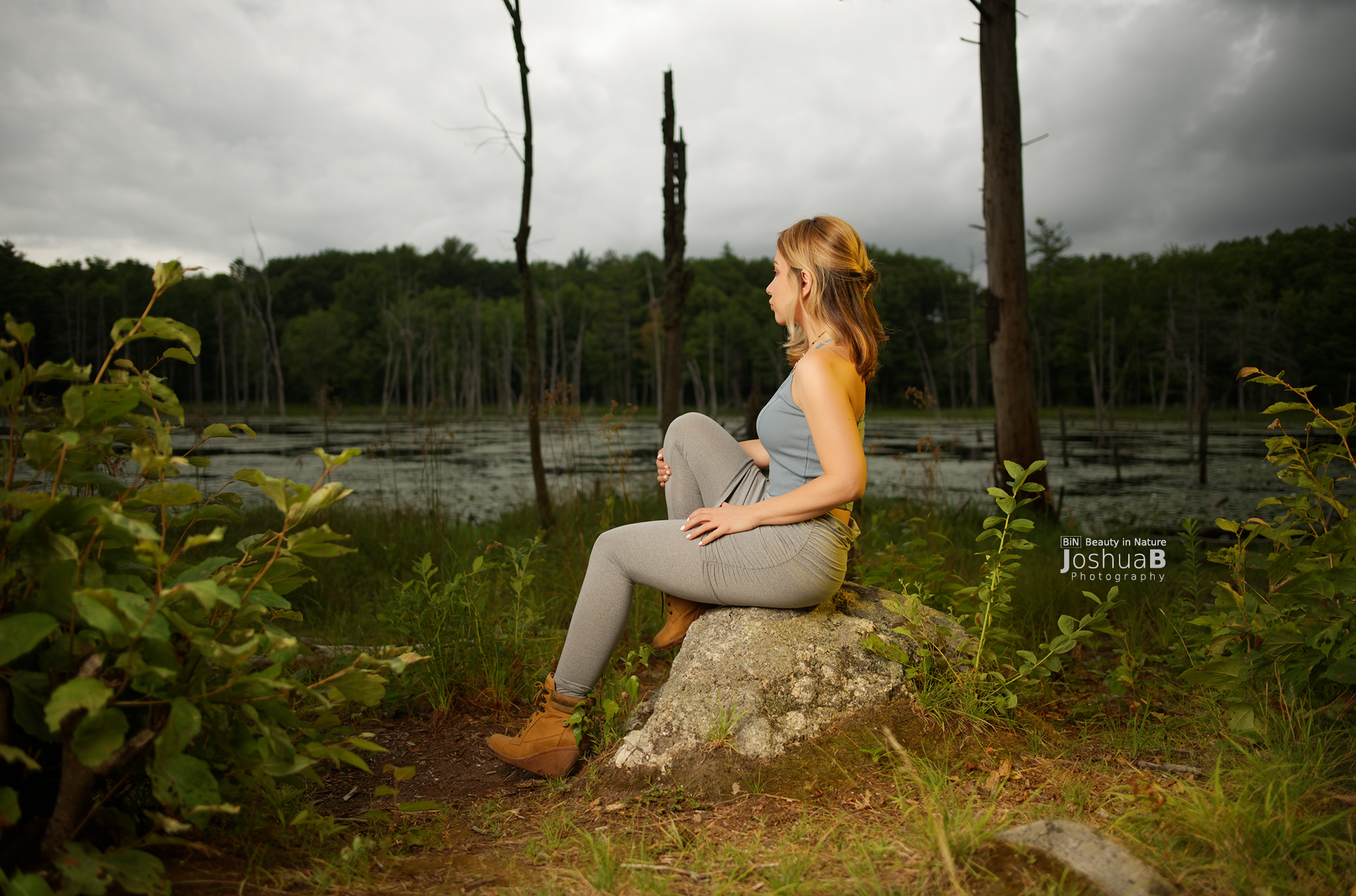 Kate Eppers blonde model side view sitting on rock