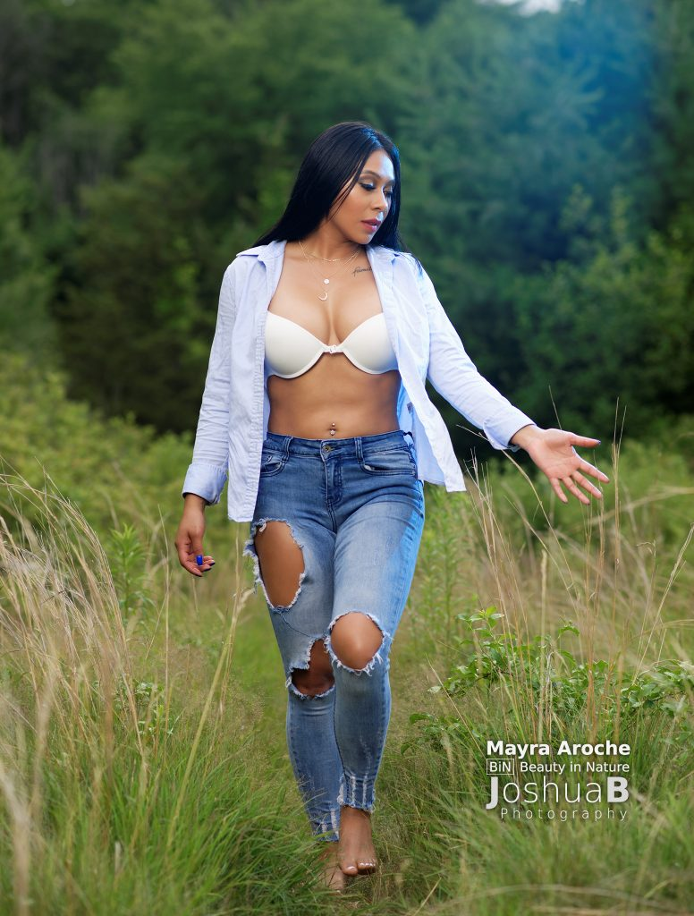 Mayra in jeans, unbottoned shirt, and bra