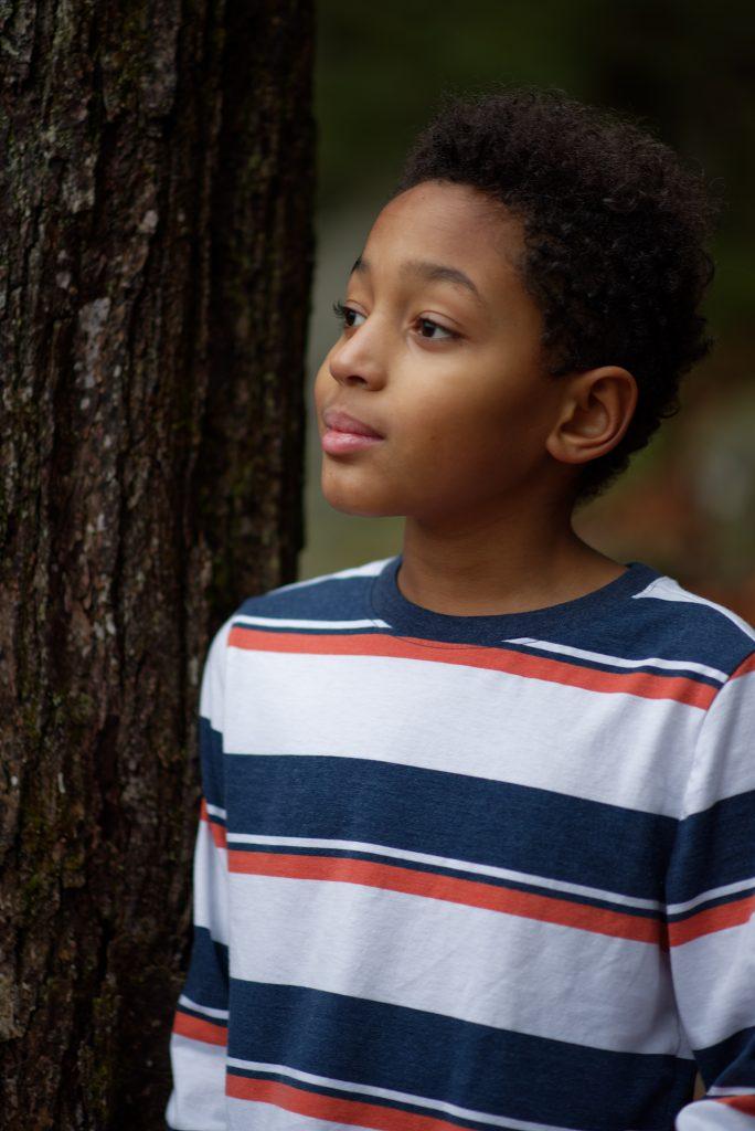Boy posing by tree